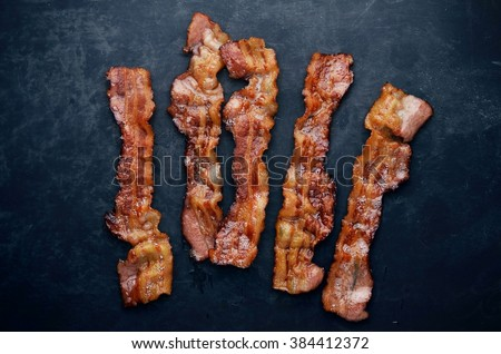 Grilled bacon with rosemary on blackboard.