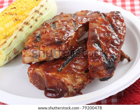 Grilled barbecue spareribs and ear of corn on a plate