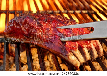 Grilled BBQ Tasty Spicy Smoked Marinated Pork Ribs And Fork At Summer Party. Hot Charcoal Grill With Flaming Embers In The Background - stock photo
