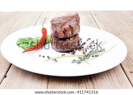 grilled beef fillet medallions with thyme and red hot chili pepper on white plate over wood table - stock photo
