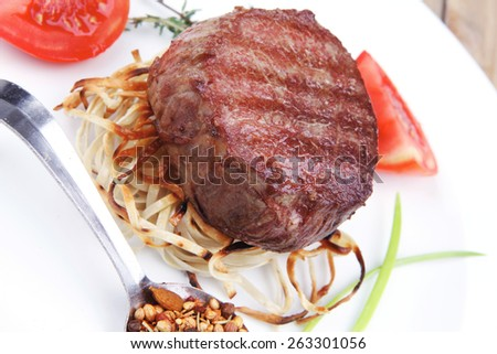 grilled beef fillet pieces on noodles with tomatoes dry spices and green thyme twigs on white plate over wood - stock photo