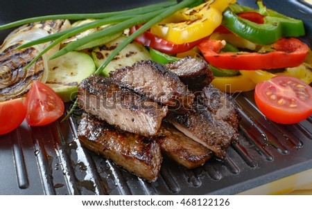 Grilled beef meat on grill with grilled vegetables in the background.