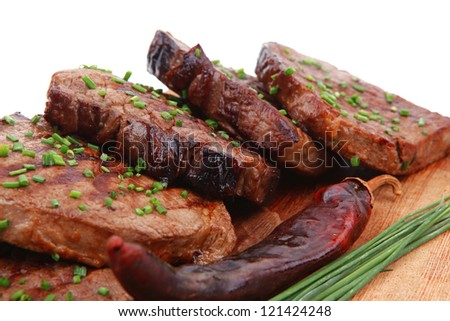 grilled beef meat on wooden plate with chives and thyme isolated on white background