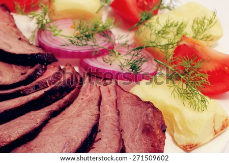 grilled beef meat steak with fried potatoes and tomatoes on white plate - stock photo