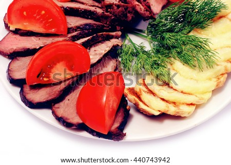 grilled beef meat steak with fried potatoes and tomatoes on white plate isoalted over white - stock photo