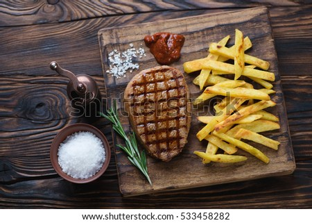 Grilled beef medallion with potato in a rustic wooden setting, high angle view