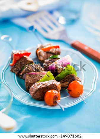 grilled beef shishkabobs on table with blue plate - stock photo