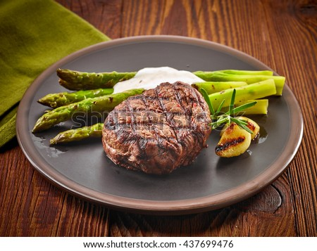 grilled beef steak and asparagus and garlic sauce on dark plate - stock photo