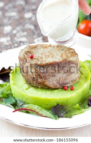 Grilled beef steak, green mashed potatoes with peas, herbs, pour out sauce - stock photo