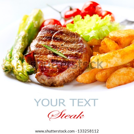 Grilled Beef Steak Meat with Fried Potato, Asparagus and Cherry Tomato. Steak Dinner. Food - stock photo