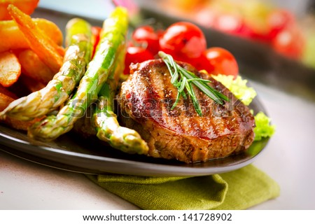 Grilled Beef Steak Meat with Fried Potato, Asparagus and Cherry Tomato. Steak Dinner. Food. BBQ Grill. Berbecue - stock photo