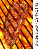 Grilled beef steak on a fire hot barbecue grill. - stock photo