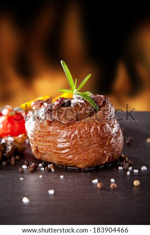 Grilled beef steak on black stone table, fire flames on background - stock photo