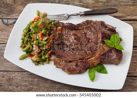 grilled beef steak with ground pepper and basil on wooden table - stock photo