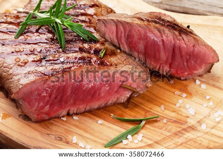 Grilled beef steak with rosemary, salt and pepper on cutting board - stock photo