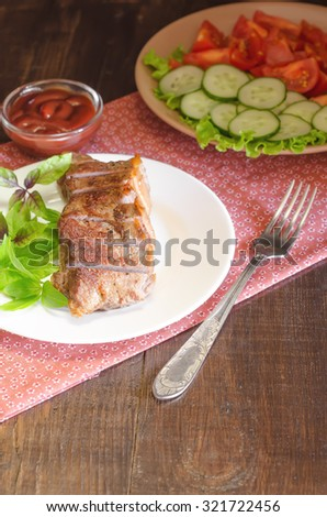 Grilled beef steak with salad and sauce on wooden table at white plate. Salad with tomatoes and cucumbers and sauce barbecue.  - stock photo