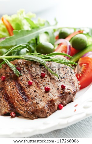 Grilled beef steak with salad on a plate - stock photo
