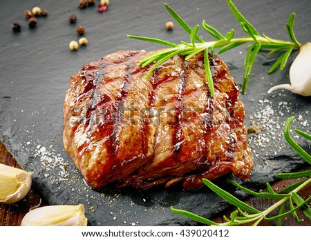 grilled beef steak with spices on black stone cutting board