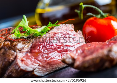 Grilled Beef steak with vegetable decoration. Grilled porterhouse steak on slate board.