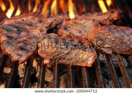 Grilled beef steaks and flaming grill in background - stock photo