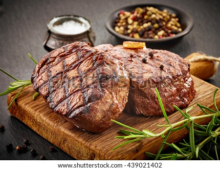 grilled beef steaks with spices on wooden cutting board - stock photo