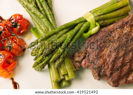 Grilled beef tenderloin with asparagus and tomatoes - stock photo