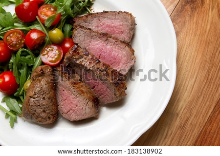Grilled beef tenderloin with cherry tomatoes and arugula on a white plate - stock photo