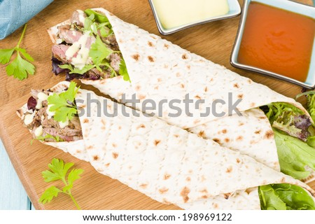 Grilled Beef Wraps - Griddled sirloin steak, sliced and wrapped in a flatbread served with blue cheese sauce and salad. Overhead shot. - stock photo
