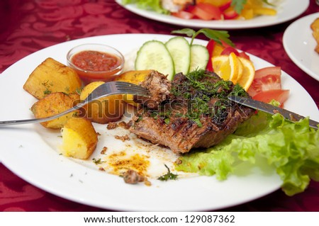 Grilled beefsteak, baked potatoes and vegetables with fork and knife.