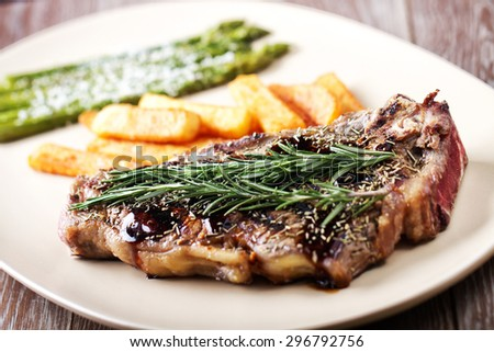 Grilled beefsteak with french fries and asparagus - stock photo