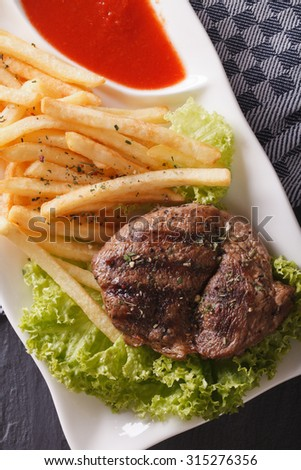 Grilled beefsteak with french fries and vegetables served on a plate close-up. vertical