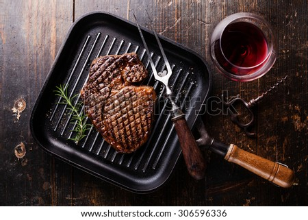 Grilled Black Angus Steak Ribeye on grill iron pan on wooden background with wine - stock photo