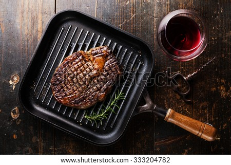 Grilled Black Angus Steak Ribeye on grill pan and red wine on wooden background - stock photo
