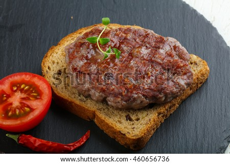 Grilled burger cutlet with bread, tomato and thyme