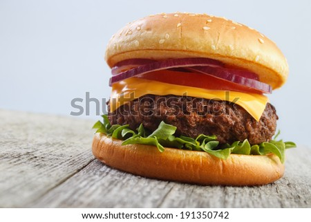 Grilled burger on wooden board with gray background - stock photo
