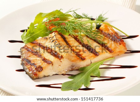 grilled carp fillet decorated with lemon and herbs