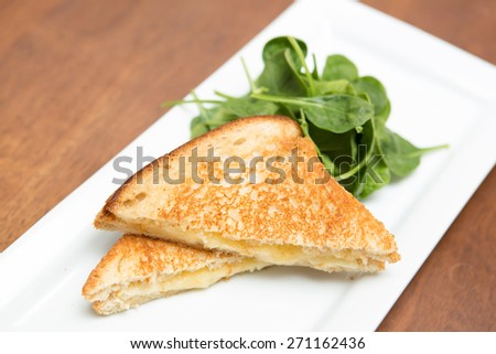 Grilled cheese sandwich and spinach salad on white plate on wood table. - stock photo