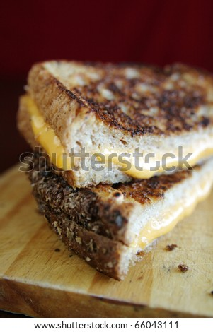 Grilled cheese sandwich with melted cheese on wood plate - stock photo