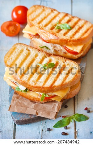 Grilled cheese sandwiches with chicken and tomatoes on a rustic wooden board. - stock photo