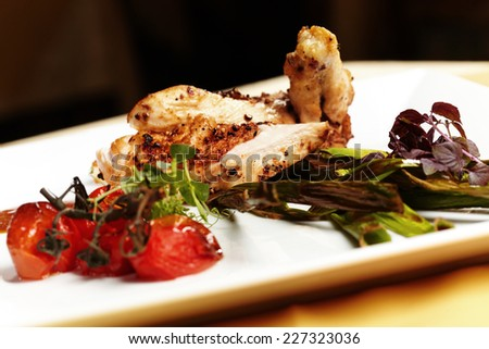 Grilled chicken breast and served with vegetable on white plate - stock photo