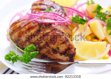 Grilled chicken breast closeup with parsley and lemon