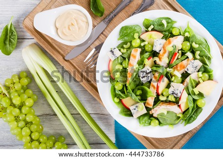grilled chicken breast, grapes, celery, spinach,  cheese and apple salad on a white dish on a cutting board with fork and knife, view from above - stock photo