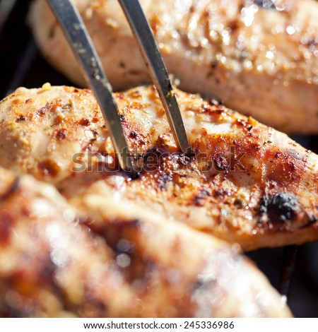 Grilled chicken breast on barbeque, cooking process - stock photo