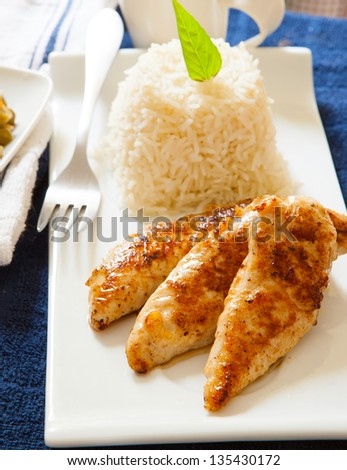grilled chicken breast served with basmaty rice on white tray - stock photo
