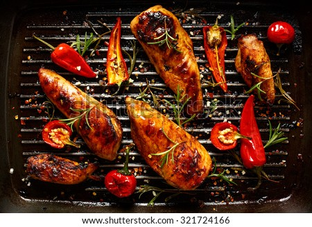 Grilled chicken breast spiced with chili peppers and rosemary - stock photo