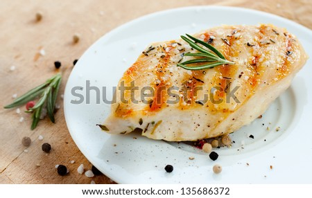 Grilled chicken breast with rosemary on white plate with wooden background - trendy rustic composition - stock photo