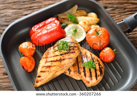 Grilled chicken breasts and vegetables on the grill pan - stock photo