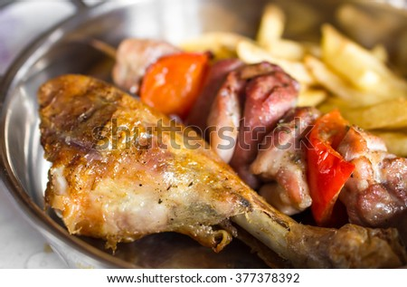 Grilled chicken drumstick, meat cooked on a spit and French fries. - stock photo
