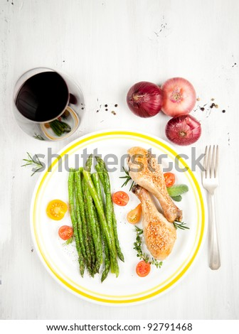 Grilled Chicken Drumsticks Served with Young Asparagus and Tomatoes - stock photo