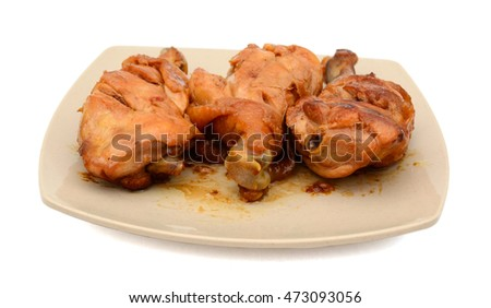grilled chicken drumsticks with fish sauce on plate isolated on white